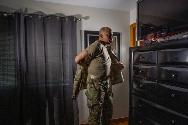 """Chief Warrant Officer 4 Phillip Brashear, a U.S. Army Reserve command chief warrant officer for the 80th Training Command, puts on his uniform jacket during an Army Reserve video production at his home in Sandston, Va., Jan. 22, 2020. Brashear is a helicopter pilot with combat experience and the son of Carl Brashear, the first African-American master diver in U.S. Navy's history who lost his leg during a tragic accident on a diver mission off the coast of Spain in 1966. Carl Brashear's life story about overcoming physical and racial adversity was featured in the Hollywood film """"Men of Honor"""" starring Cuba Gooding Jr. and Robert De Niro. Phillip Brashear has more than 38 years of military service between the U.S. Navy Reserve, the U.S. Army National Guard and the U.S. Army Reserve. He spent the majority of his Army career as a helicopter pilot with deployments to Bosnia and Iraq."""