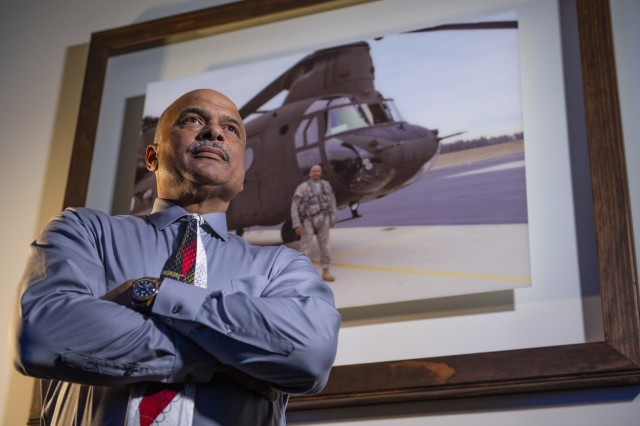 """Phillip Brashear, a weapons system manager for the Defense Logistics Agency and a U.S. Army Reserve warrant officer, poses next to a picture of him with a CH-47D Chinook helicopter he flew for the Army, at his job in Richmond, Va., Jan. 23, 2020. Phillip Brasher is the son of Carl Brashear, the first African-American master diver in U.S. Navy's history who lost his leg during a tragic accident on a diver mission off the coast of Spain in 1966. Carl Brashear's life story about overcoming physical and racial adversity was featured in the Hollywood film """"Men of Honor"""" starring Cuba Gooding Jr. and Robert De Niro. Phillip Brashear has more than 38 years of military service between the U.S. Navy Reserve, the U.S. Army National Guard and the U.S. Army Reserve. He spent the majority of his Army career as a helicopter pilot with deployments to Bosnia and Iraq."""