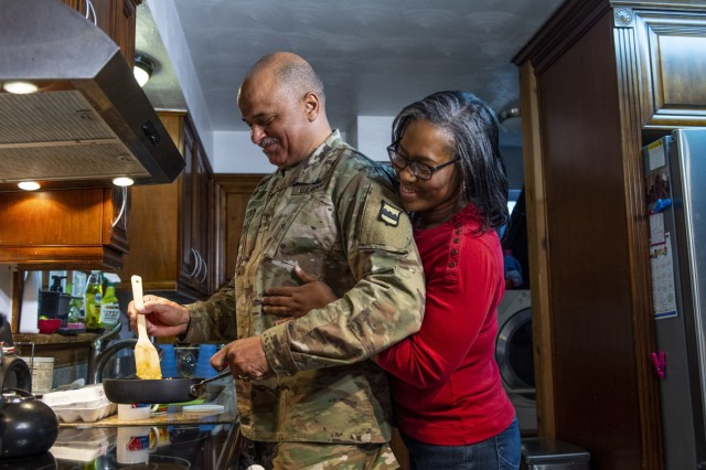 """Sandra Brashear hugs her husband, Chief Warrant Officer 4 Phillip Brashear, a U.S. Army Reserve command chief warrant officer for the 80th Training Command, during a video production shoot for the U.S. Army Reserve at their home in Sandston, Va., Jan. 23, 2020. Brashear is a helicopter pilot with combat experience and the son of Carl Brashear, the first African-American master diver in U.S. Navy's history who lost his leg during a tragic accident on a diver mission off the coast of Spain in 1966. Carl Brashear's life story about overcoming physical and racial adversity was featured in the Hollywood film """"Men of Honor"""" starring Cuba Gooding Jr. and Robert De Niro. Phillip Brashear has more than 38 years of military service between the U.S. Navy Reserve, the U.S. Army National Guard and the U.S. Army Reserve. He spent the majority of his Army career as a helicopter pilot with deployments to Bosnia and Iraq."""
