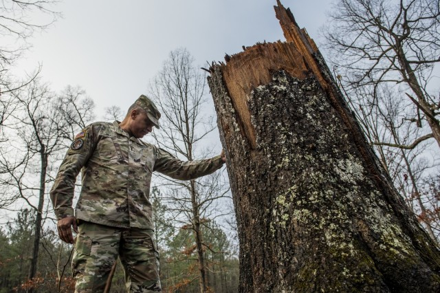 """Chief Warrant Officer 4 Phillip Brashear, a U.S. Army Reserve command chief warrant officer for the 80th Training Command, pays respect Jan. 25, 2020, to the site where a warrant officer died during a lighting strike that knocked over a large oak tree at Fort Pickett, Va. The tree fell during a brigade-level training exercise in the summer of 2019, killing Chief Warrant Officer 2 Kevin P. Sullivan. Brashear came to Pickett to participate in a foot march along with warrant officer candidates attending the Regional Training Institute on Jan. 25, 2020. Brashear is a helicopter pilot with combat experience and the son of Carl Brashear, the first African-American master diver in U.S. Navy's history who lost his leg during a tragic accident on a diver mission off the coast of Spain in 1966. Carl Brashear's life story about overcoming physical and racial adversity was featured in the Hollywood film """"Men of Honor"""" starring Cuba Gooding Jr. and Robert De Niro. Phillip Brashear has more than 38 years of military service between the U.S. Navy Reserve, the U.S. Army National Guard and the U.S. Army Reserve. He spent the majority of his Army career as a helicopter pilot with deployments to Bosnia and Iraq."""