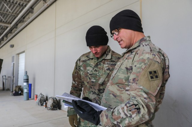 Two noncommissioned officers assigned to the 2nd Infantry Brigade Combat Team, 4th Infantry Division look at a technical manual, Jan. 29, 2020, during a Stryker drivers training course on Fort Carson, Colorado. The course was hosted by Soldiers from the 1st Stryker Brigade Combat Team, 4th Inf. Div. to help prepare Soldiers from 2IBCT for their conversion to a Stryker brigade. (U.S. Army photo by Staff Sgt. Neysa Canfield)