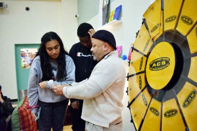 Mel Jackson, interim Camp Zama Army Community Service director, reviews a teen dating violence scenario with Kierstyn Aumua and Timothy Armstrong during the Camp Zama Youth Center Teen Dating Violence Awareness Lock-In at Camp Zama, Japan, Feb. 7.