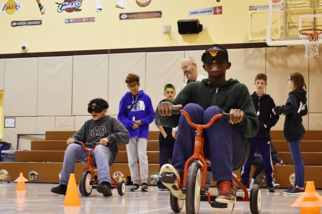 Keelyn Payne, right, and Amory Williams ride tricycles while wearing impairment goggles during the Camp Zama Youth Center Teen Dating Violence Awareness Lock-In at Camp Zama, Japan, Feb. 7.