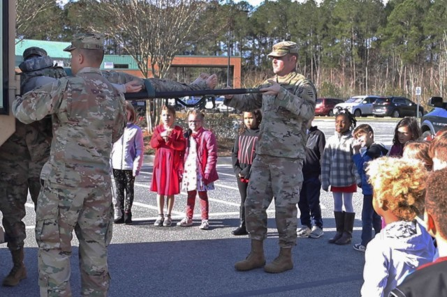 Soldiers assigned to 3rd Infantry Division litter-carry a dummy out of an M997A2 HMMWV Ambulance during a career fair hosted by George Washington Carver Elementary School in Richmond Hill, Ga., on Feb. 7, 2020. The career day gave students a chance to learn about jobs in and around their community. (U.S. Army photo by Sgt. Zoe Garbarino)