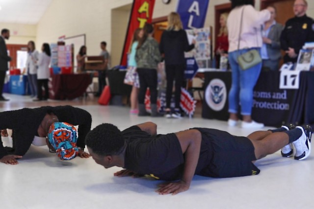 A Soldier assigned to 3rd Infantry Division Artillery performs pushups with a student attending George Washington Carver Elementary School during a career fair hosted by Carver Elementary in Richmond Hill, Ga., on Feb. 7, 2020. The career day gave students a chance to learn about jobs in and around their community. (U.S. Army photo by Sgt. Zoe Garbarino)