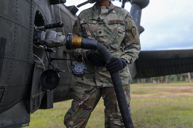 "Spc. Melissa Munisar, a Petroleum Supply Specialists assigned to Echo Co. from 2nd Battalion, 25th Aviation Regiment works together with her team to refuel three Black hawks and an Apache attack helicopter from 2-6 Cavalry Squadron, 25th Combat Aviation Brigade during training in Forward Arming and Refueling Point (FARP) procedures at Schofield Barracks, Hawaii Feb. 5, 2020. Soldiers practice fueling procedures by utilizing a field expedient method commonly referred to as FATCOW. This method consists of using the CH-47F Chinook helicopter from B. Co, 3-25 ""Hammerheads"" as a fuel source for other aircraft. The CH-47 can carry several 800 gallon fuel system tanks in its cabin where are then used to refuel other aircraft. This method allows for Forward Arming and Refueling Points (FARP) in areas where ground resources may not be feasible."