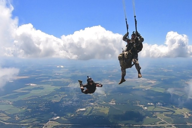 Staff Sgt. Corey Riser, an Airborne and Special Operations Test Directorate Test Parachutist and Video Flyer at Fort Bragg, North Carolina, observes Sgt. 1st Class Jacob Droski as he conducts Modular Lightweight Load-Carrying Equipment (MOLLE) 4000 rucksack risk reduction testing; completing his pull sequence over Maxton Airfield, North Carolina.