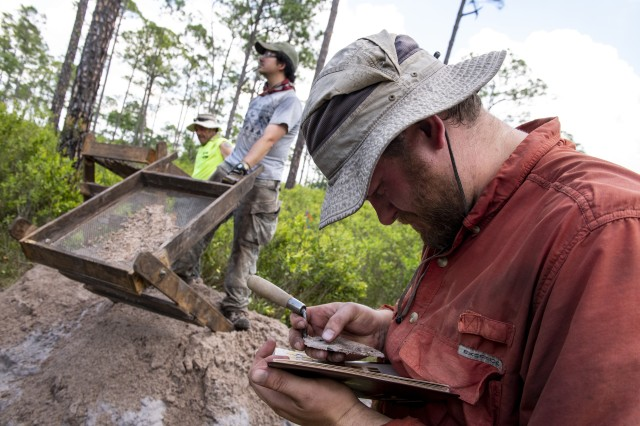 Matthew Crabtree, a dig crew chief working for the Air Force, compares soil color on a Munsell soil chart for later analysis in the lab at Avon Park Air Force Range in Florida, April 18, 2019. The Air Force is excavating a newly found archaeological site and is going through the process of making it eligible for placement on the National Register of Historic Places.