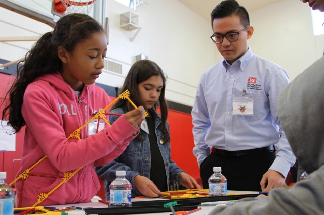 U.S. Army Corps of Engineers Los Angeles District USACE Structural Civil Engineer Lenard Lee Tran encourages students to design and build bridges during a West Point Academy Science, Technology, Engineering, and Mathematics event at Stephen M. White Middle School in Carson, California.