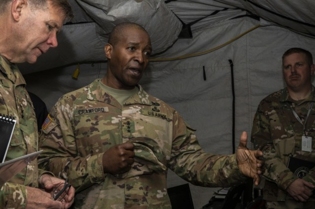 Lt. Gen. Bruce T. Crawford (center), the Army's chief information officer/G6, and Lt. Gen. Stephen G. Fogarty (left). commanding General of U.S. Army Cyber Command, visit a tactical operations center during the Joint Warfighting Assessment on Joint Base Lewis-McChord, Wash., May 1, 2019. Crawford was named the 2020 Black Engineer of the Year. He is only the second Army officer to receive the award.