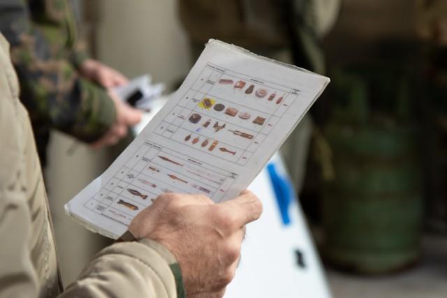 A Peshmerga soldier studies various types of unexploded ordnance