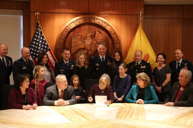 """New Mexico Gov. Michelle Lujan Grisham signs HB 30 """"Expedited Licensure for Military Families and veterans,"""" Feb. 26 at the state capitol. The legislation, the culmination of years of work to support reciprocity and ease of occupational licensing for military members, veterans and their families, is expected to come into effect July 1. Representatives from the state legislature, military installations in New Mexico, and civic leaders took part in the signing."""