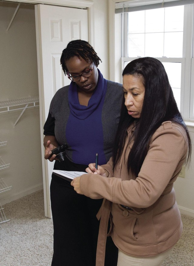 Debora Rivera, left, Garrison industrial hygienist, and Elena Gold, PhD, Fort Belvoir Community Hospital industrial hygienist, document the condition of a remediated home in Dogue Creek Village, Monday.