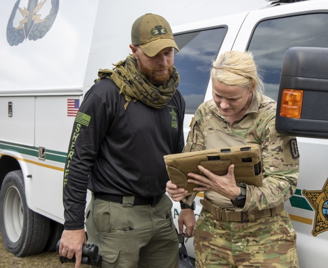 Staff Sgt. Heather Cockrell, 744th Ordnance Company (EOD), and Christopher Heavey, Orange County Count Sheriff's Office, examine an X-ray of an explosive device left on a commuter bus during Raven's Challenge on March 4, 2020. Raven's Challenge is an annual series of events that enhances the interoperability of explosive ordnance disposal personnel and public safety bomb squads from military and government agencies in a realistic, domestic, tactical environment.