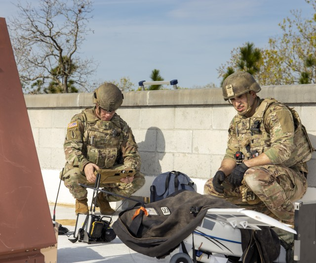 Staff Sgt. David Ervin (left) examines an X-ray of an unmanned aircraft system with internal and external explosives as Staff Sgt. Jonathan Pando observes the device during Raven's Challenge on March 4, 2020. Both of the 744th Ordnance Company (EOD) Soldiers were required to figure out how to render the device safe from a rooftop at Camp Blanding, Florida. Raven's Challenge is an annual series of events that enhances the interoperability of explosive ordnance disposal personnel and public safety bomb squads from military and government agencies in a realistic, domestic, tactical environment.