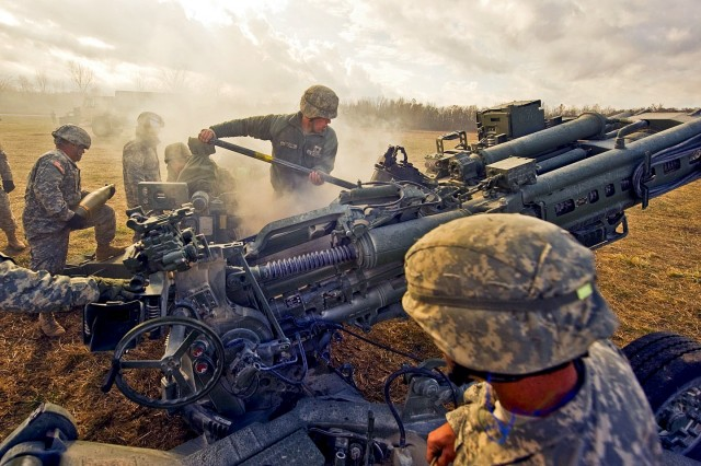 Indiana National Guard Soldiers work together to smoothly execute a fire mission using their M777 Howitzers at Camp Atterbury Joint Maneuver Training Center in central Indiana.