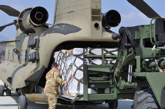 Soldiers from the U.S. Army Medical Materiel Center-Korea's 563rd Medical Logistics Company loads Class VIII medical supplies onto a CH-47 helicopter with guidance from the 2ID/2CAB crew chief on March 24, 2020. (U.S. Army photo by Shawn Hardiek)