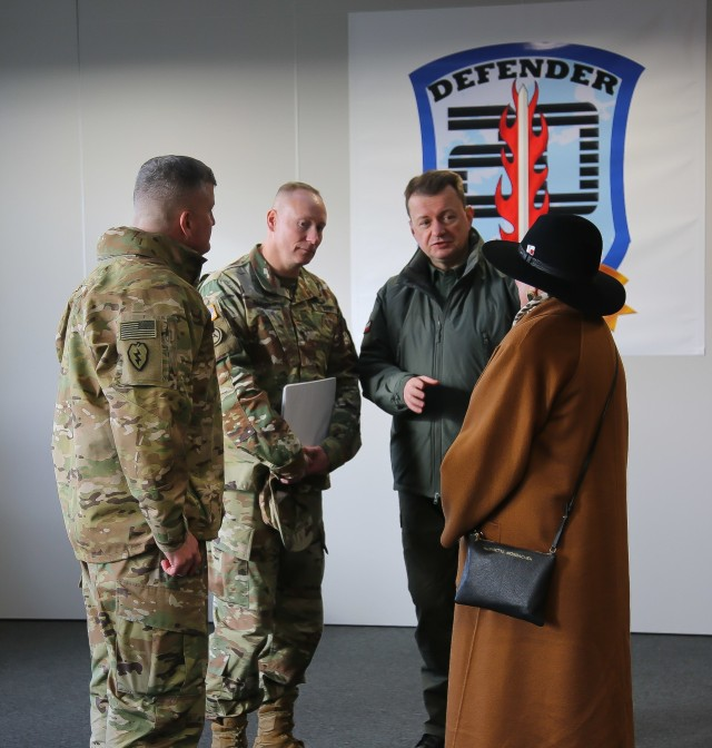 Col. Timothy O'Connor (left), 1st Infantry Division Forward Commander, speaks with U.S. and Polish officials during a troop engagement event at the Ziemsko Airfield, Poland, on March 11, 2020.