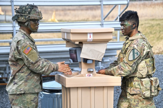 U.S. Soldiers assigned to 2nd Armored Brigade Combat Team, 1st Cavalry Division use a hand-washing station to reduce the potential spread of COVID-19 during training at the 7th Army Training Command's Grafenwoehr Training Area, Germany, March 19, 2020. (U.S. Army photo by Gertrud Zach)