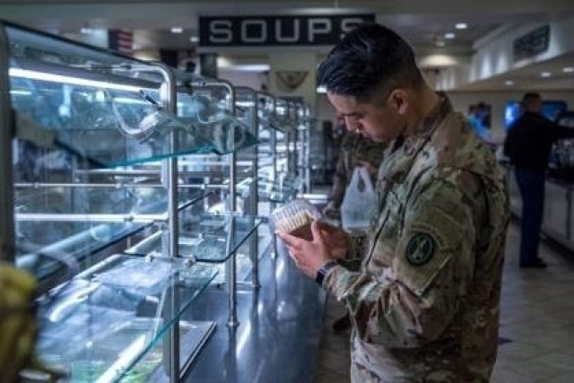 Pvt. Eduardo Ortiz, an infantryman with Honor Guard Company, 4th Battalion, 3d U.S. Infantry Regiment (The Old Guard), selects a prepackaged item at the dining facility, DFAC, on Joint Base Myer - Henderson Hall as part of the shift to a grab-and-go serve system, March 19, 2020. The shift is part of the DFAC's implemented changes to combat COVID-19.