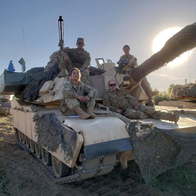1st Lt. Hanna Rozzi (lower left) sits with her M1 Abrams tank crew. Rozzi is only one of 137 female armor officers in the Army.