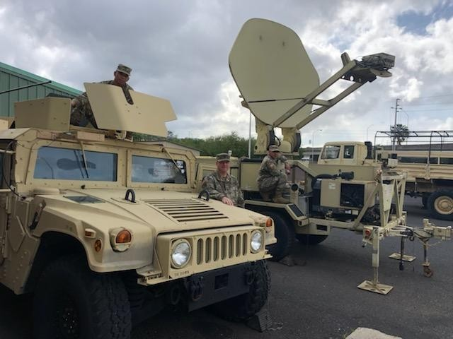 (From left to right) Sgt. Edimar Purganan, in the M1151 weapons turret, Sgt. 1st Class Benjamin Cox, and Sgt. Jason Baddo, on the wheel of the Satellite Transportable Terminal (STT), take a quick photo as they prepare the communications capability in the vehicles for eXportable Combat Training Capability at Fort Chaffee, Arkansas.The Satellite Transportable Terminal (STT) is a highly transportable and mobile satellite system, which operates in conjunction with the Joint Network Node and Command Post Node. It is designed to establish secure voice, video and data communications virtually anytime and anywhere and will be used with the JBC-P to establish secure communications.Photo by Lt. Col. Steven S. Bittle