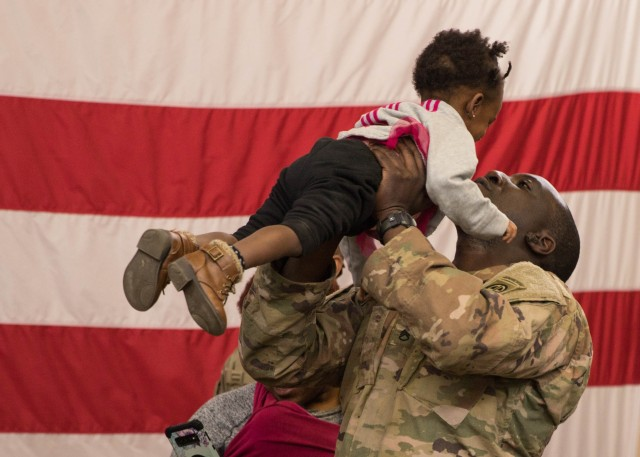 A Paratrooper from 1st Brigade Combat Team, 82nd Airborne Division holds his daughter during a redeployment ceremony at Fort Bragg, N.C., February 20, 2020. The ceremony was held to welcome home Paratroopers who deployed in support of the New Year's Eve Immediate Response Force activation to the Central Command theater of operations.