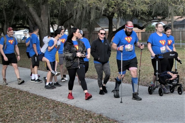Sgt. First Class Jeff Dawson, pictured with the red, white and blue headband, is joined by friends, family, and members of his chain of command as he walks a 5k in Tampa, Florida, Feb. 15, 2020. This marks an significant milestone for Dawson, an explosive ordnance disposal team leader, with the 28th Ordnance Company (EOD), 192nd Ordnance Battalion (EOD), 52nd Ordnance Group (EOD), on his road to recovery since being shot in combat in July 2019 where he suffered nerve damage. (U.S. Army photo by SSG Adam Hinman)