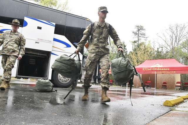 A Fort Jackson, S.C., basic combat training graduate retrieves his duffel bags from a commercial bus as Sgt. 1st Class Jessy Kingrey looks on during new arrival processing at the 59th Ordnance Brigade's Ordnance Resiliency and Training Center. He was one of 800 troops transported here to continue their initial entry training. To prevent the spread of COVID-19, they were placed on sterilized buses, seated in spaced-apart intervals, medically screened before departure and upon arrival, and accompanied by cadre members from Fort Jackson.