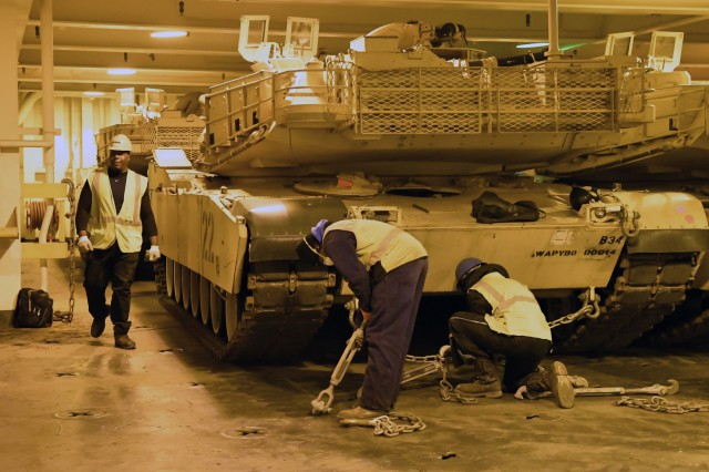 Contract workers secure A1 Abrams tanks inside he Bob Hope-class roll-on/roll-off ship USNS Benavidez February 22, 2020 in support of DEFENDER-Europe 20. This ship will carry military equipment to the European theater as part of almost 6,000 pieces of cargo that the Military Surface Deployment and Distribution Command will process through ports in the Gulf of Mexico. (U.S. Army photo/Kimberly Spinner)