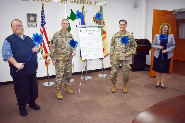 From left, Stan Austin, manager of the U.S. Army Garrison Japan Family Advocacy Program; USAG Japan Command Sgt. Maj. Billy Norman; Col. Thomas Matelski, commander of USAG Japan; and Jen Partridge, director of USAG Japan Army Community Service, stand with the garrison's Child Abuse Awareness Month proclamation in garrison headquarters, Camp Zama, Japan, April 1. They hold blue pinwheels because normally the proclamation reading includes a planting of pinwheels outside the ACS building, but this year officials held it inside with limited attendance due to COVID-19.