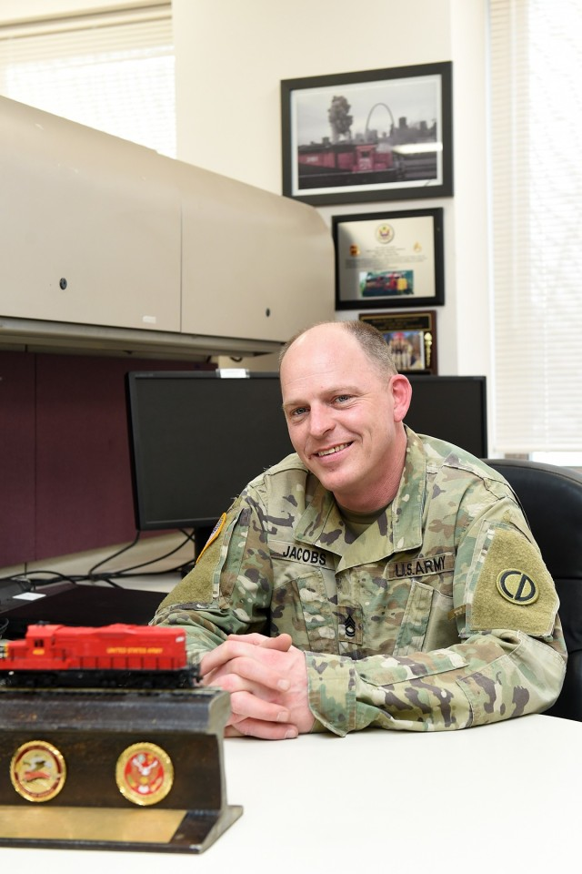 Army Reserve Sgt. 1st Class James Jacobs, Training NCO, Headquarters & Headquarters Company, 85th U.S. Army Reserve Support Command, pauses for a photo at his desk. Jacobs is an 88 Uniform (Railway Specialist) with more than 20 years of experience in Army rail operations. Jacobs is one of only two Active, Guard & Reserve Soldiers holding the primary military occupational specialty of 88 Uniform in the Army. (U.S. Army Reserve photo by Sgt. David Lietz)
