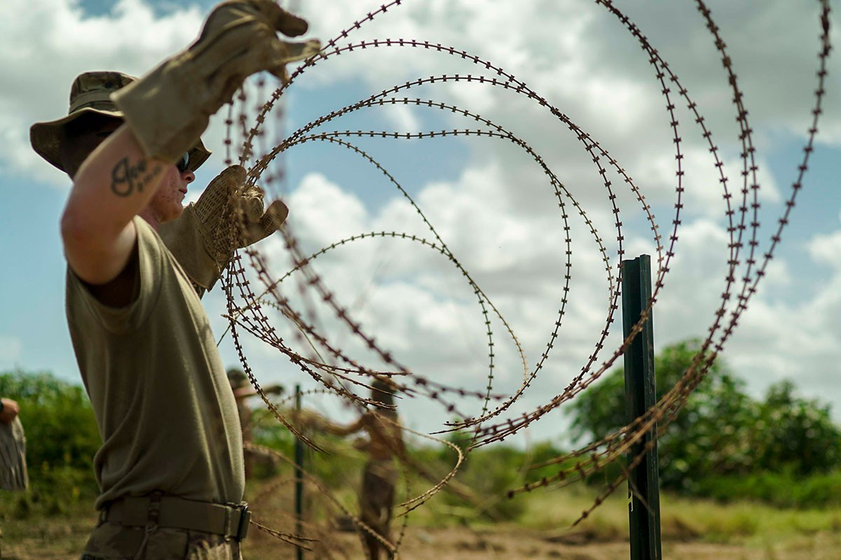 U.S. Army Private Alexander Hering, Rifleman, 2nd Battalion, 506th Infantry Regiment, 3rd Brigade Combat Team, 101st Airborne Division (Air Assault), places concertina wire on a fence post in east Africa, Jan. 20, 2020. Soldiers from the 101st Airborne Division are assigned to the East Africa Response Force and provide the ability to rapidly respond to events spanning a vast area of responsibility.