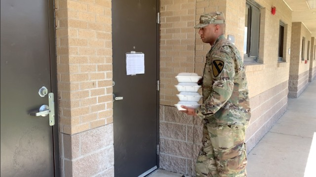A Greywolf Soldier delivers lunch to quarantined Soldiers in the barracks in support of protecting the force and flattening the curve.