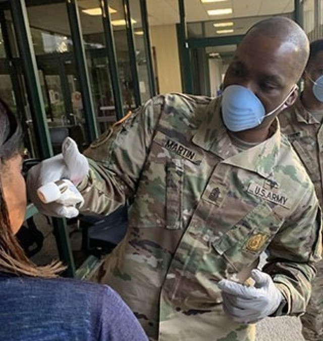 Winn Army Community Hospital senior enlisted leader, Sgt. Maj. Quincy Martin helps out a screening station on Fort Stewart March 31 as patients and staff prepare to enter the hospital. (Photo by Zach Rehnstrom)