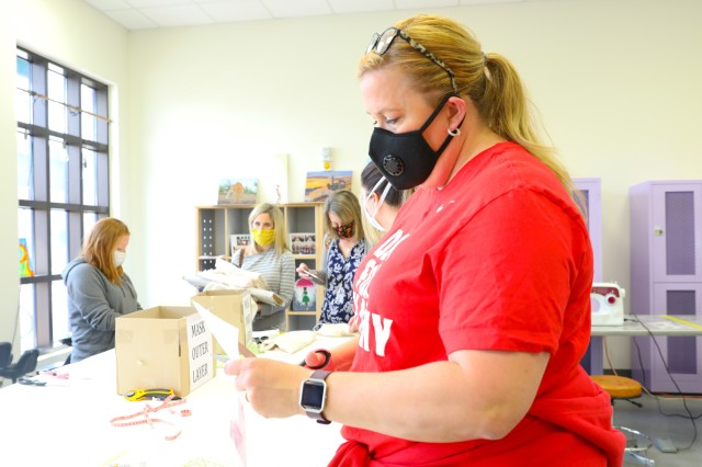 Kelly Schmidt, an active duty spouse, cuts out a template to put together masks during the coronavirus outbreak. Volunteers flocked to the Arts and Crafts Center at Camp Humpherys, South Korea, April 7, 2020. These masks are more important today because the Department of Defense provided guidance requiring anyone on DOD property to wear a mask if six feet of social distance cannot be maintained. (U.S. Army Photo by Pfc. Jillian Hix, 20th Public Affairs Detachment)