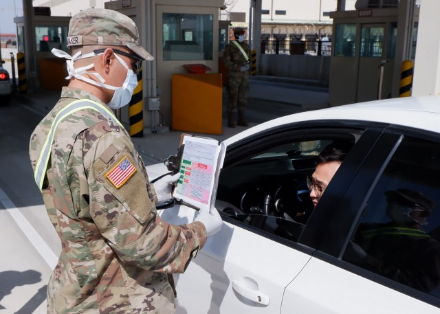 A Soldier from A Company, 1st Battalion, 18th Infantry Regiment, 2nd Armored Brigade Combat Team, Fort Riley, Kansas, interviews a personnel coming through the Adams Gate at U.S. Army Garrison-Humphreys, South Korea, for any indicators of the coronavirus. (U.S. Army photo by James Myer)