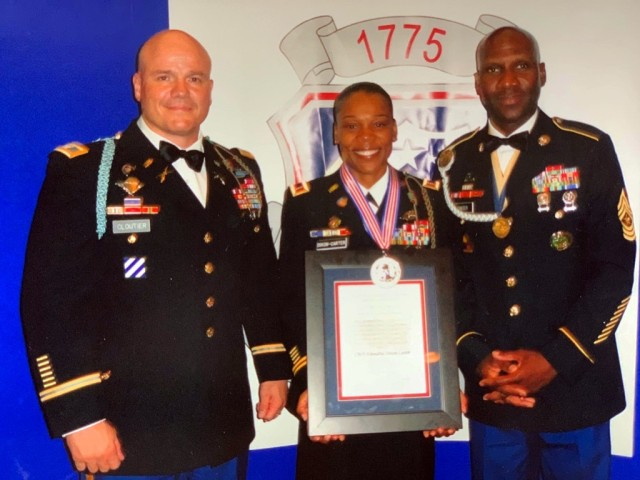 Chief Warrant Officer Yolondria Dixon-Carter receives the Warrant Officer of the Year award at the National Warrant Officer Ball at Fort Jackson, S.C., in 2011.  Presenting the award are Col. Roger L. Cloutier Jr., commander, 1st Brigade, 3rd Infantry Division, and her husband, Sgt. Maj. Emmanuel Carter.