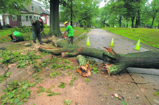 Landscaping contracters worked Sunday to clear fallen trees and limbs from roadways.   photo by Marny Malin