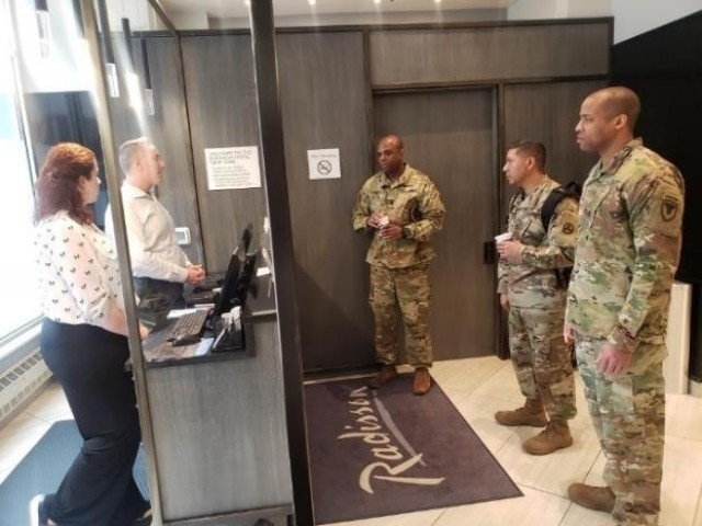 From left, Lt. Col. Jason Miles, Master Sgt. Cirildo Guerrero Jr., and Maj. Jermaine Pruitt answer inquiries from the staff at a hotel in New York City. Miles and Pruitt are deployed to New York City to provide contracting support to Soldiers from the 3rd Expeditionary Sustainment Command there for the nation's fight against the COVID-19 pandemic. Miles is the commander of Regional Contracting Center-East Contracting Support. Pruitt is the deputy commander of RCC-East Contracting Support. Guerrero is the 3rd ESC operational contract support integration cell noncommissioned officer in charge.