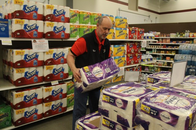 Defense Commissary Agency employee Mike Graham stocks supplies April 3, 2020, at the Fort McCoy (Wis.) Commissary. Since the installation's response to the COVID-19 pandemic began in March 2020, the Fort McCoy Commissary staff continued to take steps to protect their customers and follow recommended pandemic-response guidelines. Military commissaries worldwide, including at Fort McCoy, installed clear plastic sneeze shields in all regular checkout lanes for added extra protection for customers and cashiers during the COVID-19 outbreak. The panels are 36 inches high and range in width from 24-30 inches. Note: This photo was taken before the Department of Defense requirements on wearing masks in public were released. (U.S. Army Photo by Scott T. Sturkol, Public Affairs Office, Fort McCoy, Wis.)  Fort McCoy, Wisconsin, Commissary, Defense Commissary Agency, DeCA, COVID-19 response, coronavirus response, safety and health
