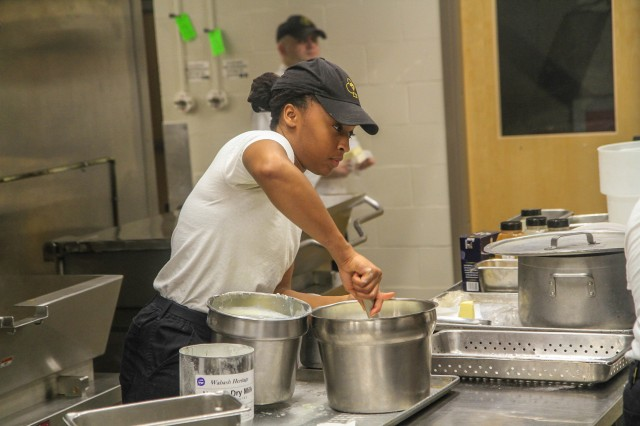"""Spc. Kayla Mitchell, culinary specialist, Headquarters and Headquarters company, 426 Brigade Support Battalion, 1st Brigade Combat Team """"Bastogne"""", 101st Airborne Division stirring ingredients for the lunch meal April 2 in the Snipes Dining Facility on Fort Campbell, Kentucky. The Snipes Dining Facility is remaining open seven days a week to ensure Bastogne Soldiers safely receive a healthy meal to sustain their physical and mental readiness during their response to COVID-19. U.S. Army photo by Maj. Vonnie Wright."""