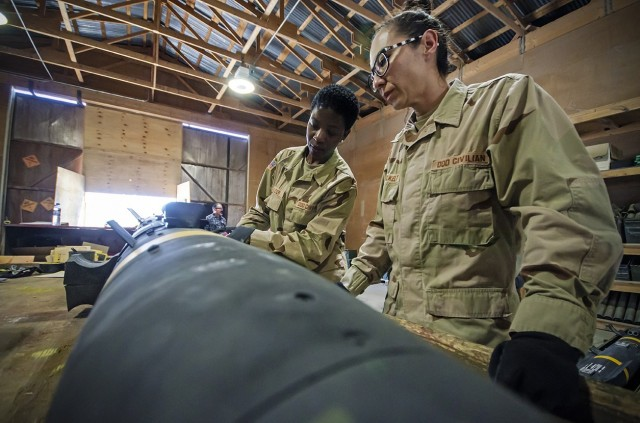 Jennifer Voelkelt (right), quality assurance specialist, ammunition surveillance, Army Field Support Battalion-Afghanistan, and Christabel Frazier (left), QASAS, AFSBn-AFG examine a Hellfire Missile during an inspection at Bagram Airfield, Afghanistan, March 31, 2018.