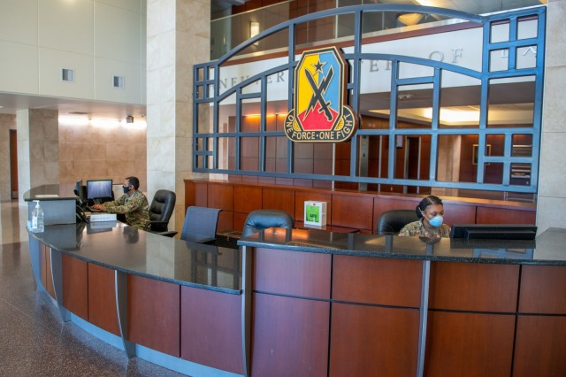FORT BENNING, Ga. – Soldiers on reception desk duty inside the headquarters of Fort Benning's Maneuver Center of Excellence April 15, wear face masks under a recent Department of Defense directive, as a precaution against the spread of COVID-19.