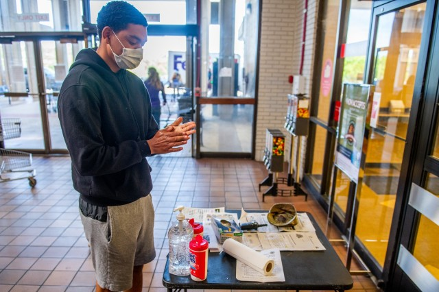FORT BENNING, Ga. – At the entrance to Fort Benning's commissary April 15, a customer cleans his hands with sanitizer placed there for patron's use, and, in keeping with a recent Department of Defense directive, wears a face mask before entering the commissary, as a precaution against the spread of COVID-19.
