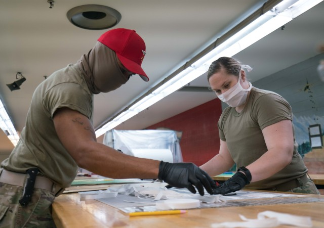 Spc. Ashley George, right, and Pfc. Kevin Cole, left, both parachute riggers with the 647th Quarter Master Company, 3rd Expeditionary Sustainment Command, assemble protective masks at Fort Bragg, N.C., on April 15, during Operation Dragon Mask. Units from across Fort Bragg were repurposed to create face masks, face shields, and other personal protective equipment to be distributed as part of the COVID-19 response. (U.S. Army Photo by Sgt. Liem Huynh)