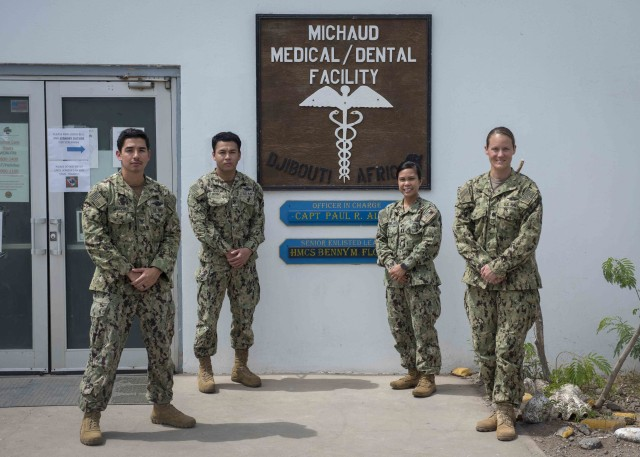 U.S. Navy personnel, from left, Hospital Corpsmen 2nd Class Jerry Marquez and Wickbol Monno, Lt. Gail Evangelista, nurse, and Cmdr. Hillary Meyer, nurse anesthetist, assigned to Naval Hospital Rota, Spain, stand in front of Michaud Expeditionary Medical Facility (EMF) at Camp Lemonnier, Djibouti, April 16, 2020. The four-member team augments critical positions within the EMF during the COVID-19 pandemic, enabling existing EMF staff to execute their primary mission of treating trauma patients. (U.S. Air Force photo by Senior Airman Dylan Murakami)
