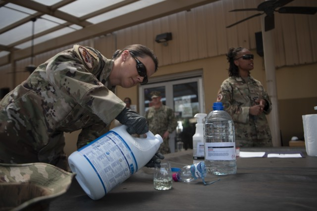 U.S. Air Force Maj. Leah Chapman (left), Combined Joint Task Force-Horn of Africa Surgeon Cell public health officer, demonstrates creating a cleaning solution using bleach and water during a training session for the high-traffic area disinfectant team at Camp Lemonnier, Djibouti, March 27, 2020. The team learned how COVID-19 and other viruses can live on non-porous surfaces, such as metal, glass, plastic, and laminated surfaces, for several days. (U.S. Air Force photo by Senior Airman Gage Daniel)