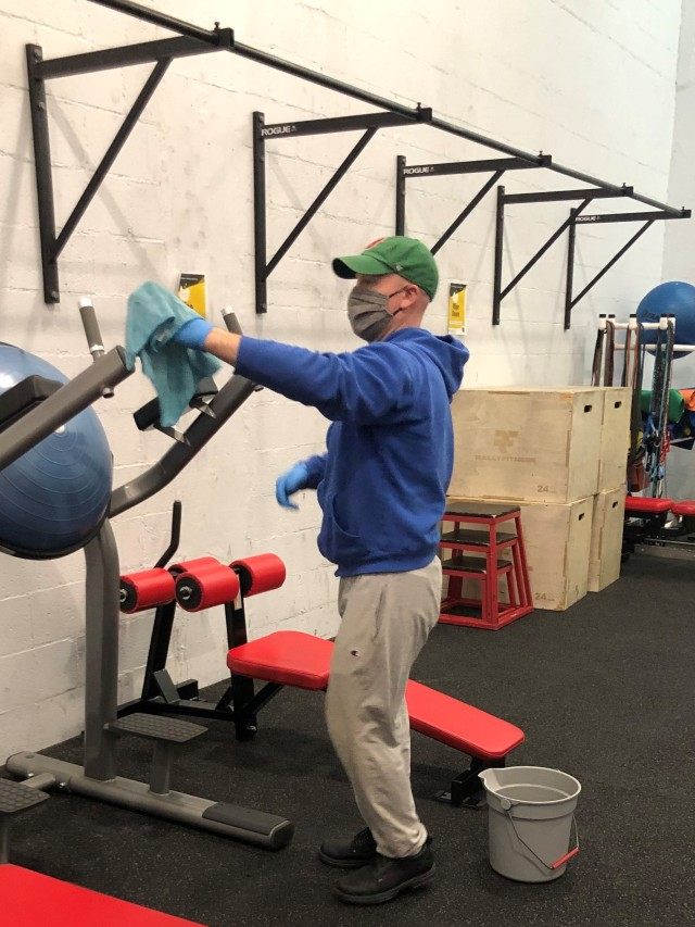 U.S. Army Garrison Alaska, Fort Greely Physical Fitness Center employee Mr. Justin Reardon cleans and sanitizes weight room equipment for patron use. The Physical Fitness Center and Indoor Track remain open honoring the garrison's commitment to provide services that maintain mission readiness.