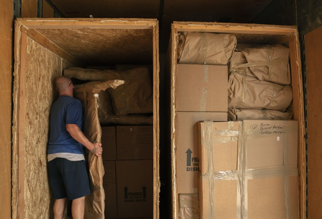 Movers load the property of a service member into crates to be transferred to a temporary storage facility in O'Fallon, Ill., July 1, 2019.  The Army has recently launched several new polices to help ease the burden of the stop-movement order, which is now extended to June 30, 2020.